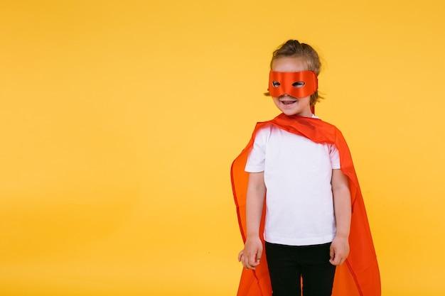 Klein blond meisje verkleed als superheldin-superheld met cape en rood masker, glimlachend en kijkend naar de zijkant, op gele achtergrond