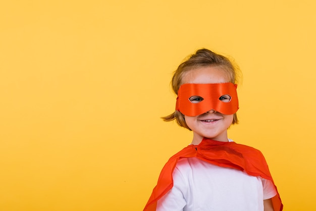 Klein blond meisje verkleed als superheldin-superheld met cape en rood masker, glimlachend, op gele achtergrond