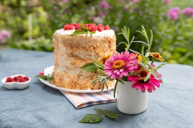 Klein boeket tuinbloemen in vaas op tafel in de tuin zelfgemaakte frambozencake op de achtergrond