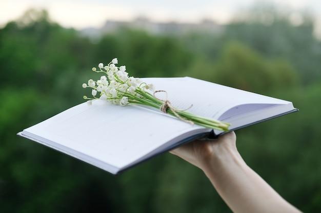 Klein boeket van lelietje-van-dalen met ambachtelijk touw in een open notitieboekje in vrouwenhand