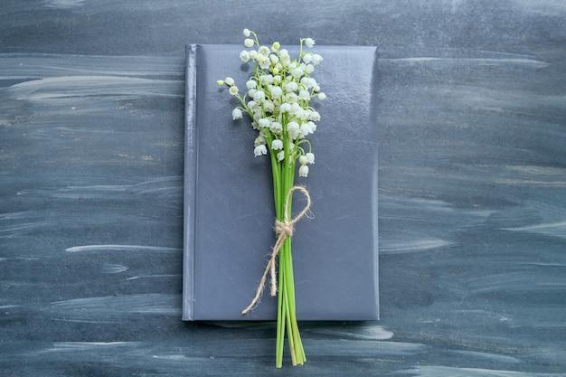 Klein boeket van lelietje-van-dalen met ambachtelijk touw op notitieboekje