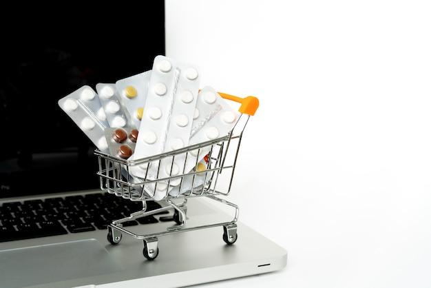 Klein boodschappenwagentje met geneesmiddelen op laptop voor het winkelen online concept.