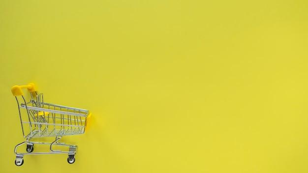 Klein boodschappenwagentje op geel.