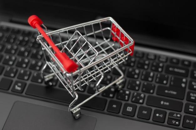Klein boodschappenwagentje op laptop om online te winkelen. online winkelconcept.