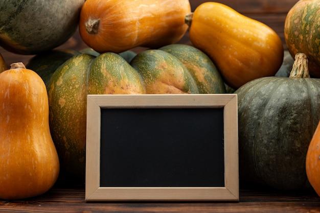 Klein bord in houten frame tegen stapel pompoenen
