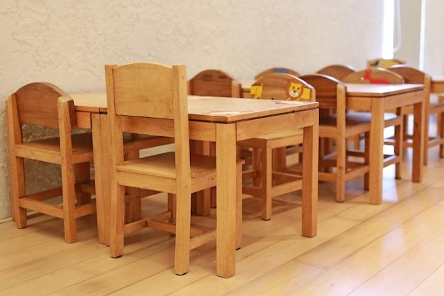 Klein bureau en stoelen voor kind in studenten klaslokaal.