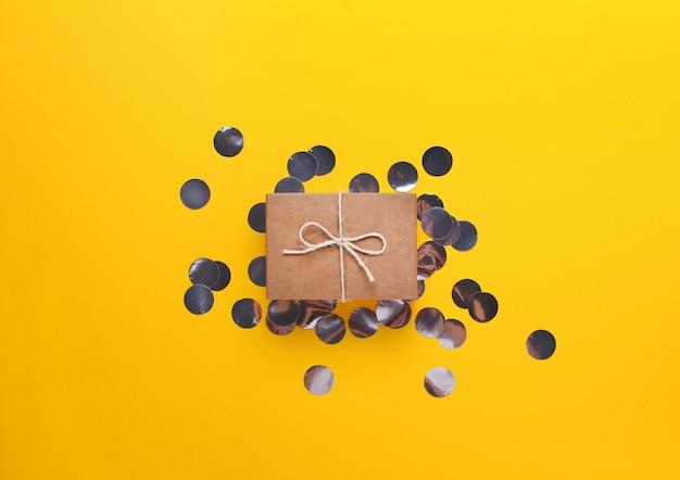 Klein cadeautje gewikkeld in ambachtelijk papier op een gele achtergrond. met zilveren confetti.