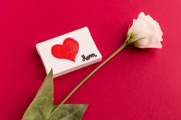 Klein canvas met hart dichtbij bloem