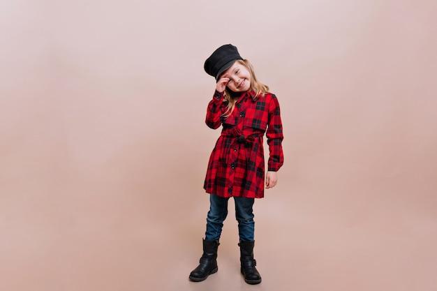 Klein charmant meisje gekleed geruit overhemd, spijkerbroek en stijlvolle pet vormt op geïsoleerde muur met echte gelukkige emoties