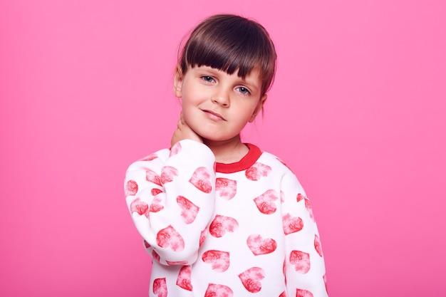 Klein charmant vrouwelijk kind met donker haar dat aan pijn lijdt, camera kijkt met fronsend gezicht, handen op haar nek houdt, geïsoleerd over roze muur.