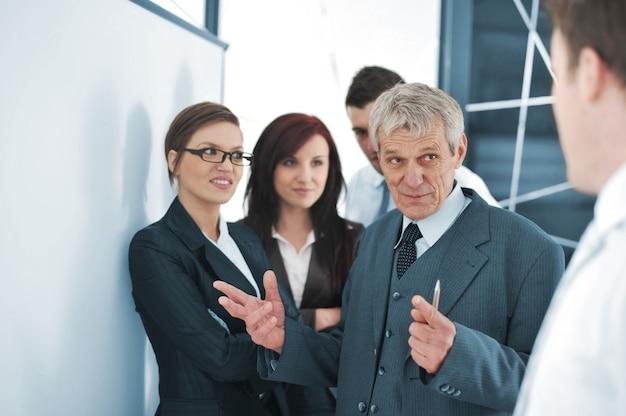 Klein commercieel team in het bureau voor een whiteboard dat een project bespreekt