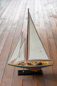 Klein decoratief model van een zeiljacht op de houten dekachtergrond