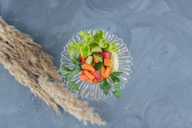 Klein deel van herderssalade naast een grote stengel van droog naaldgras op marmeren achtergrond.