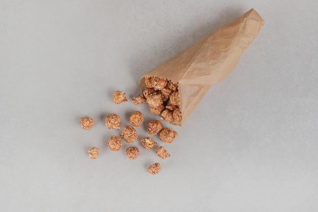 Klein deel van popcornsuikergoed in een papieren verpakking op marmeren tafel.