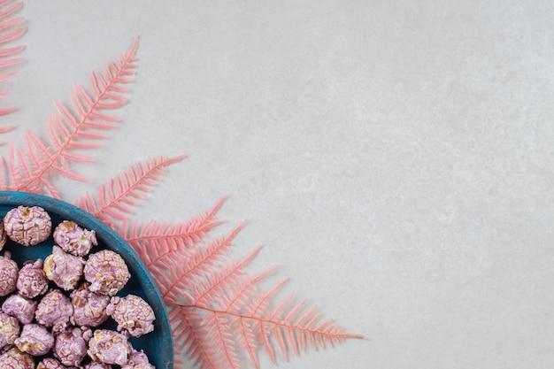 Klein dienblad van met snoep beklede popcorn die op een bos van roze bladeren op marmeren lijst rust.