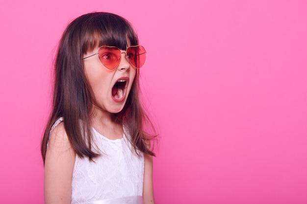 Klein donkerharig meisje ziet iets vreselijks opzij, staat verdoofd, kijkt weg, schreeuwt van afgrijzen op haar gezicht, draagt stijlvolle witte jurk, geïsoleerd over roze muur