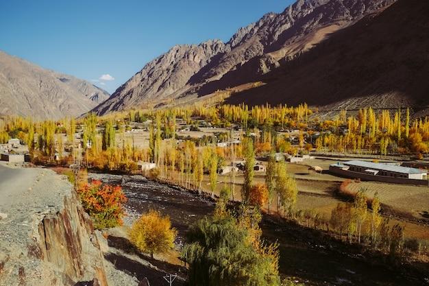 Klein dorp in gupis-vallei tegen hindu kush-bergketen in de herfst