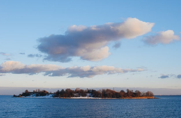 Klein eiland in de golf van finland in de ondergaande zon en mooie hemel. rusland, kronstadt.