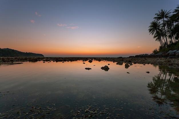Klein eiland met prachtige lichte zonsondergang of zonsopgang boven zee en mooi