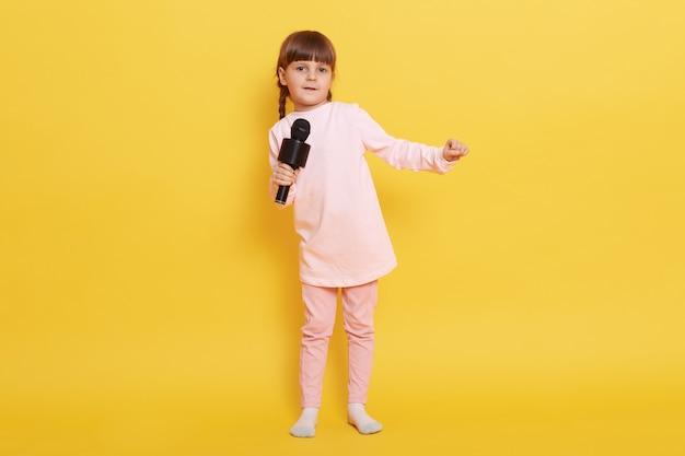Klein europees meisje zingen met microfoon, kijkt naar camera, zingen in karaoke, optreden, show maken, concert regelen, kleine zanger presteert.