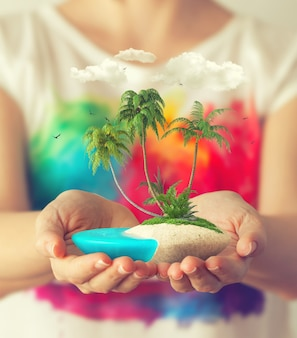 Klein fantastisch eiland met tropische palmen in handen van vrouwen