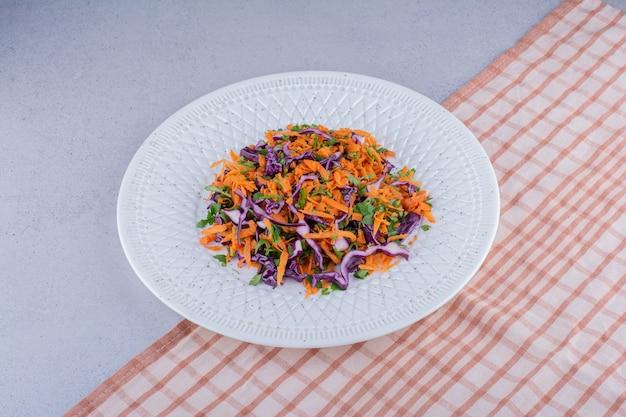 Klein gedeelte van kool en wortelsalade op marmeren achtergrond.