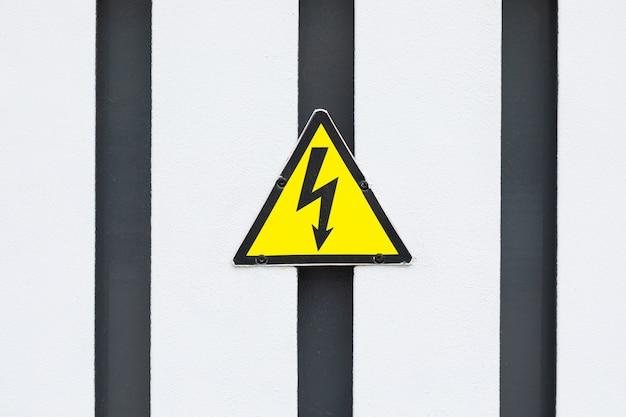 Klein geel driehoekig bord met zwarte bliksem op zwart-wit gestreepte muur