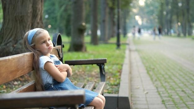 Klein geïrriteerd kindmeisje dat alleen op een bankje in het zomerpark zit