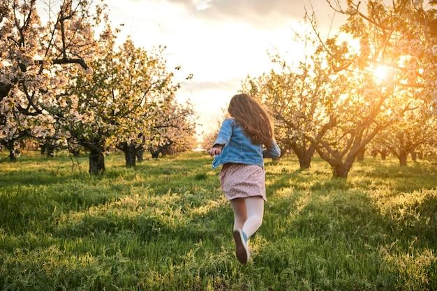 Klein gelukkig kindmeisje dat onder bloeiende appelbomen loopt met witte bloemen in een bloeiende tuin