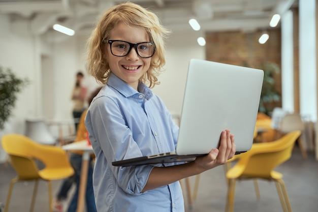 Klein geniaal portret van een slimme jongen met een bril die naar de camera glimlacht terwijl hij een laptop vasthoudt en gebruikt