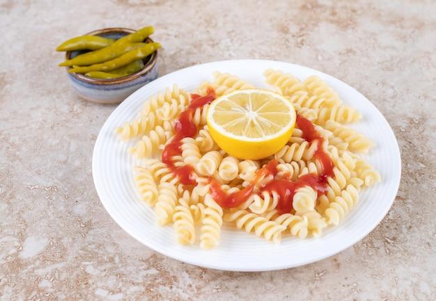 Klein gepekelde peperportie met een portie macaroni op marmeren ondergrond.