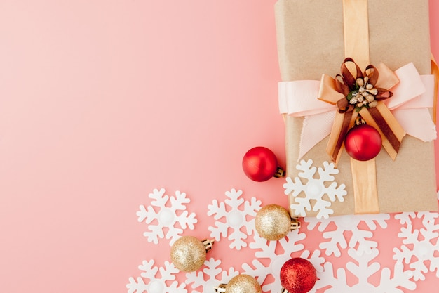 Klein geschenk verpakt met lint op roze achtergrond