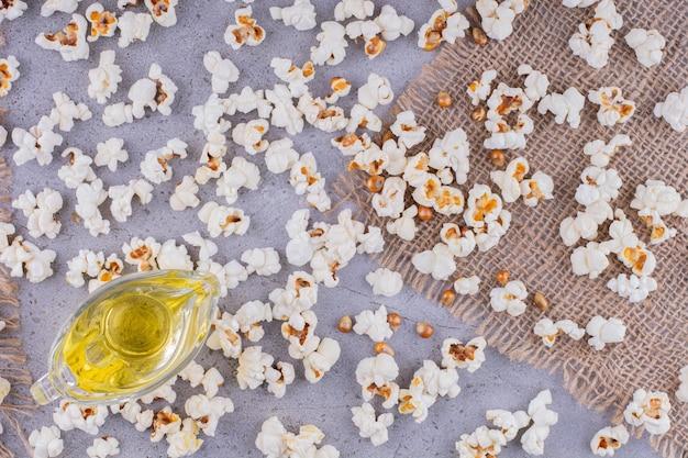 Klein glas olie in het midden van een puinhoop van verspreide popcorn op marmeren achtergrond. hoge kwaliteit foto