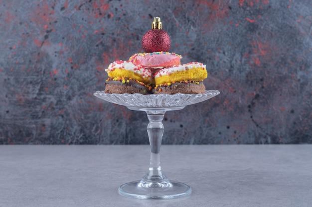 Klein glazen voetstuk met een stapel donuts op een marmeren ondergrond
