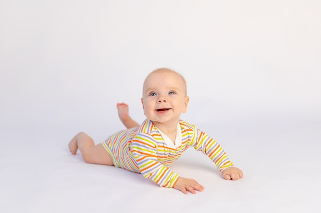Klein glimlachend babymeisje van 6 maanden oud ligt in een lichte romper. een gezond en gelukkig kind.