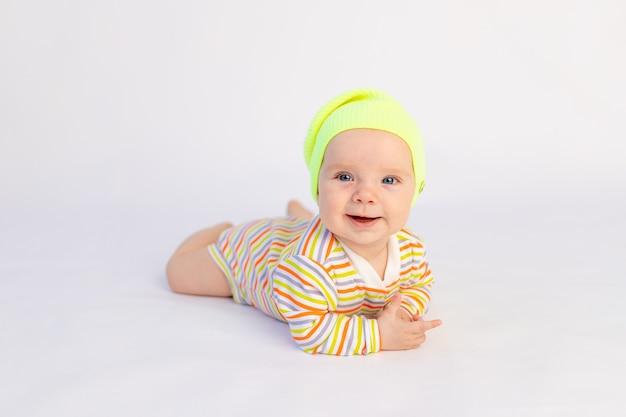 Klein glimlachend babymeisje zes maanden oud ligt geïsoleerd