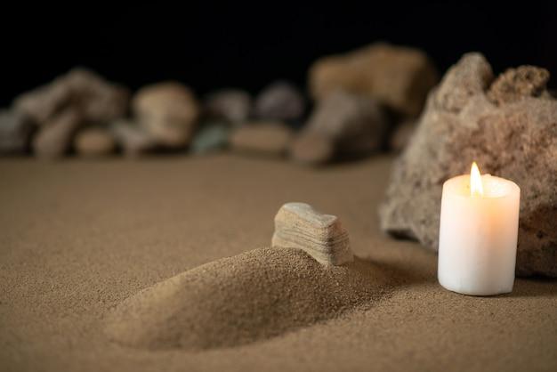 Klein graf met kaars en stenen op zand begrafenis oorlogsslachtoffer