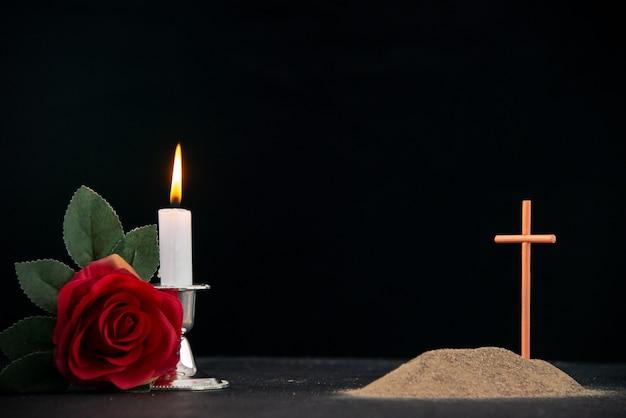 Klein graf met kaarsen en bloemen als herinnering op donkere ondergrond