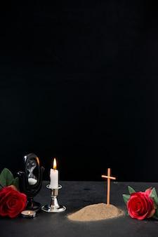Klein graf met rode bloem en brandende kaars als herinnering op donkere ondergrond