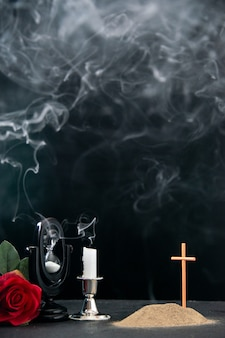 Klein graf met rode bloem en vuurloze kaars als herinnering op donkere ondergrond