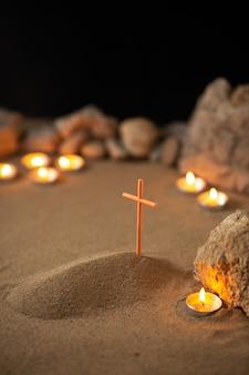 Klein graf met stenen en brandende kaarsen op donkere ondergrond
