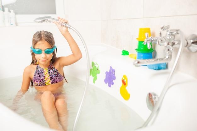 Klein grappig meisje in blauwe badbril glimlacht charmant terwijl ze water uit de douche over zichzelf giet