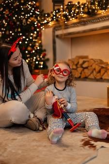 Klein grappig meisje met kerstbril en moeder in modieuze feestelijke pyjama's zitten op de vloer bij de kerstboom