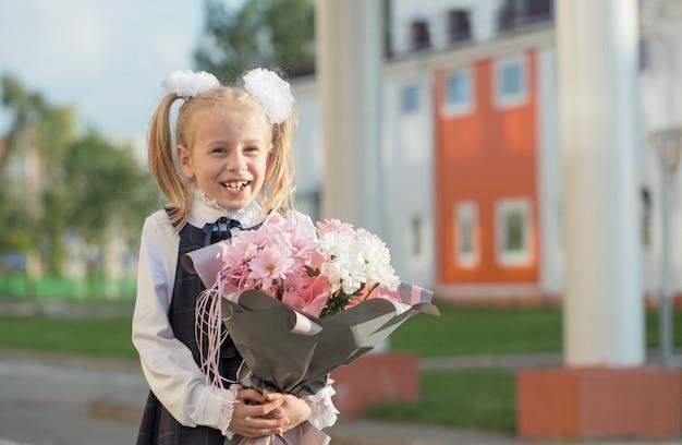 Klein grappig schoolmeisje met boeket gaat op zonnige dag naar school