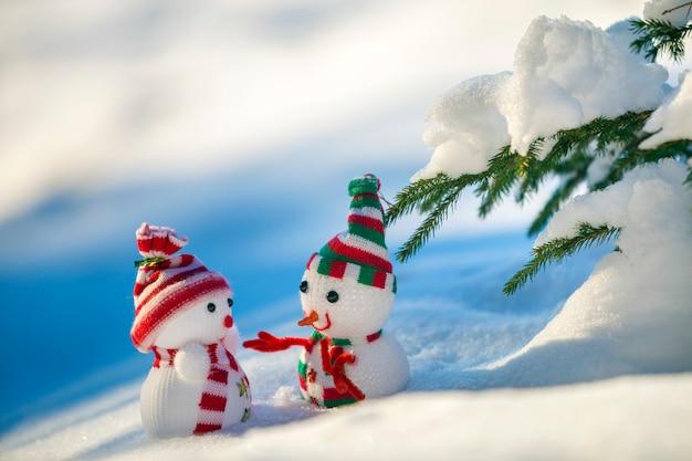 Klein grappig speelgoed baby sneeuwpop in gebreide mutsen en sjaals in diepe sneeuw buiten in de buurt van pijnboomtak.