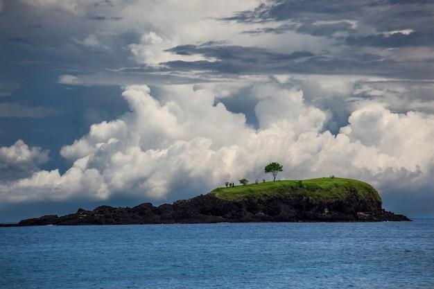 Klein groen eiland in indische oceaan. contrast bewolkte hemel en kalme zee-oppervlak. krachtig en rustig natuurlandschap.