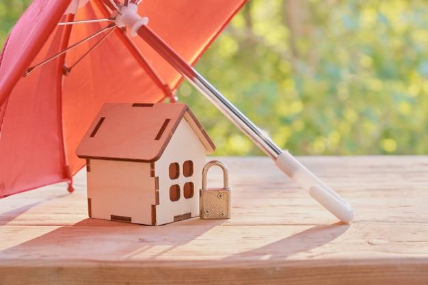 Klein hangslot, rode koepelparaplu en blokhuismodel op houten plankoppervlak, groene natuurlijke achtergrond, onroerendgoedbeschermingsconcept, verzekering