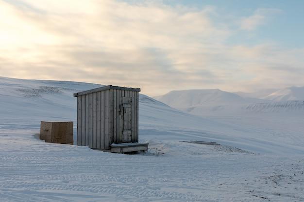 Klein houten bijgebouw hut in het midden van het noordpoollandschap in de winter
