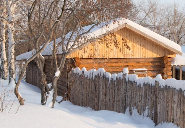 Klein houten blokhuis in een sneeuwbos