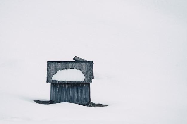 Klein houten handgebouwd huis in een bos dat in sneeuw op een sneeuwheuvel wordt behandeld